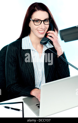 La femme parlant au téléphone et en travaillant sur l'ordinateur portable Banque D'Images