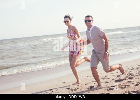 Couple heureux en lunettes de soleil. Sur la plage se tenant la main. Tourné en extérieur dynamique Banque D'Images