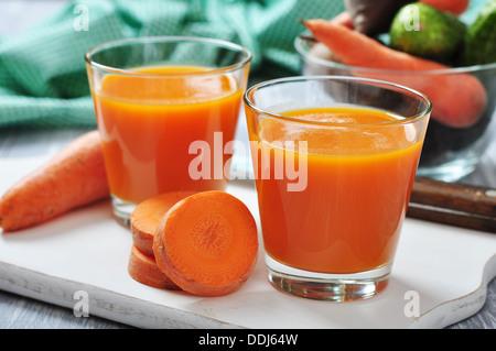 Verres de jus de carotte et les carottes fraîches sur planche à découper en bois Banque D'Images