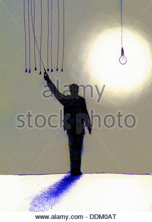 Businessman choisissant l'interrupteur pour allumer l'ampoule sur Banque D'Images