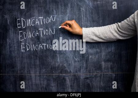 La main le mot éducation sur un tableau noir avec un morceau de craie Banque D'Images