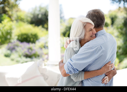 Senior couple hugging on patio Banque D'Images