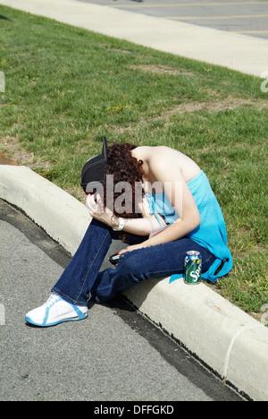 Teen femme ivre se trouve sur le bord d'un trottoir de la rue après avoir bu trop d'alcool Banque D'Images