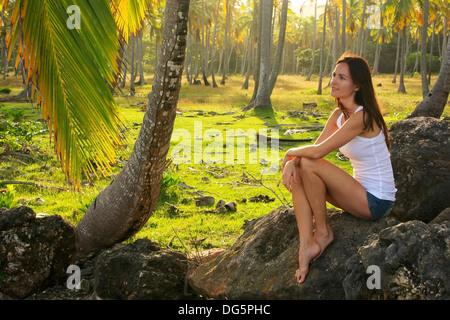Jeune femme assise sur des rochers dans les arbres de noix de coco grove beach, Las Galeras, péninsule de Samana, Banque D'Images