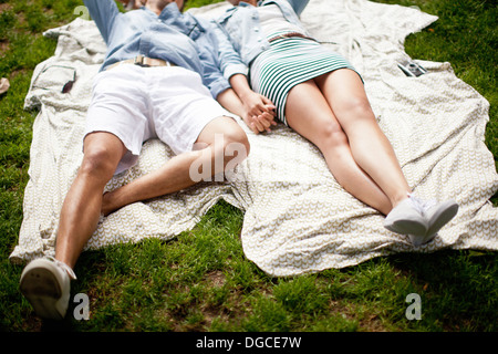 Young couple lying in park and holding hands Banque D'Images