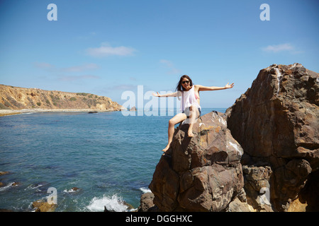 Jeune femme assise sur des rochers, Palos Verdes, California, USA Banque D'Images