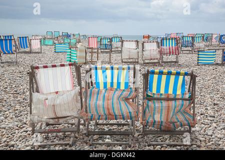 Chaises longues par fort vent sur la plage à la bière. Banque D'Images