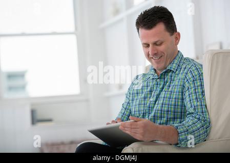 Un homme assis dans un fauteuil, à l'aide d'une tablette numérique. Banque D'Images