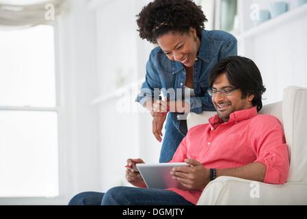 La vie de bureau. Un homme et une femme à la recherche d'une tablette numérique à. Banque D'Images
