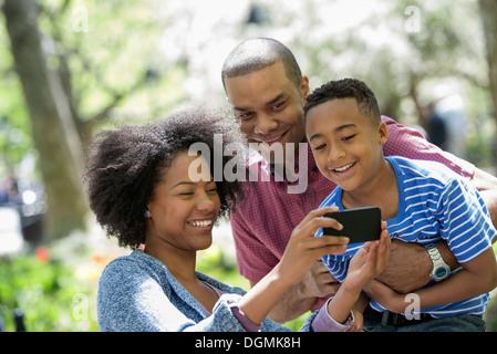 Une famille dans le parc sur une journée ensoleillée. Prendre des photos avec un téléphone intelligent. Banque D'Images