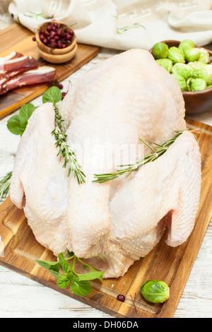 La Turquie cru entier sur planche à découper en bois, des légumes, du jambon et des épices. Vue d'en haut Banque D'Images