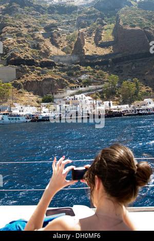 Une femme prend une photo de la jetée de Skala, l'ancien port de Santorin, en navigation au sud de Santorin, Grèce Banque D'Images