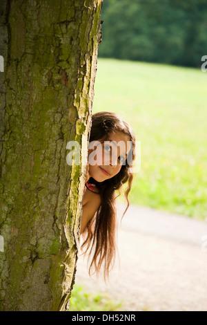 Smiling girl à la recherche de derrière un arbre Banque D'Images