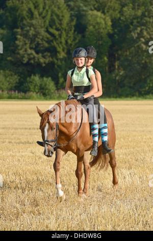 Deux jeunes filles (le port de casque et protecteur de dos) équitation ensemble à l'arrière d'un cheval de sport Banque D'Images
