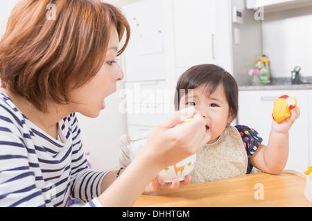 Mère de nourrir bébé dans la cuisine Banque D'Images