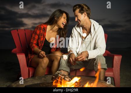 Jeune couple toasting marshmallow dans camp, San Diego, California, USA Banque D'Images