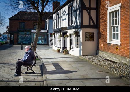 Personnes âgées homme seul assis à Royal Wootton Bassett dans un quartier calme dimanche matin Banque D'Images