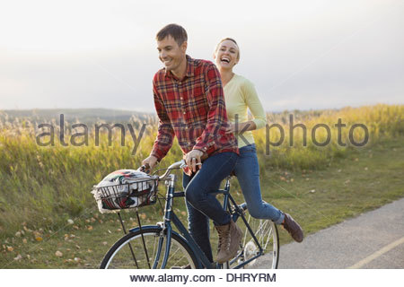 Heureux couple cycling on country road Banque D'Images