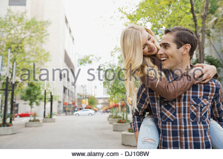 Playful couple walking on city street Banque D'Images