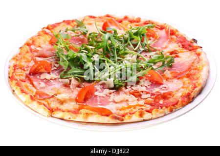 Pizza au jambon et à la roquette sur un fond blanc. Chemin de détourage. Banque D'Images