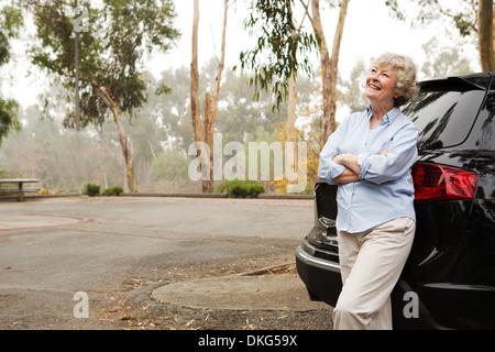 Senior woman standing contre l'arrière du véhicule noir Banque D'Images