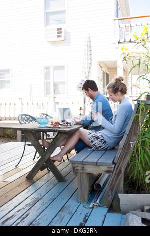 Couple on patio avec ordinateur portable et mobile, Breezy Point, Queens, New York, USA Banque D'Images