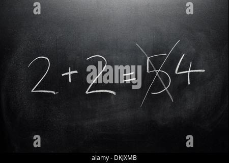 Un tableau noir avec la somme 2+2 écrit dessus en blanc de craie avec bonne et de mauvaises réponses. Banque D'Images