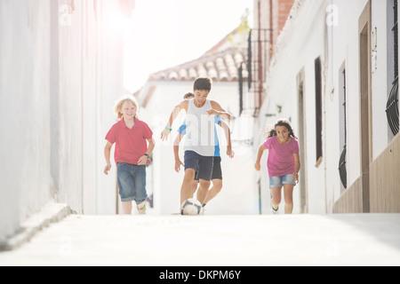 Les enfants jouent au soccer sur alley Banque D'Images