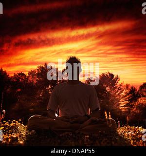 Shaolin Kung Fu instructor méditant dans la nature pendant le coucher du soleil, assis les jambes croisées sous Banque D'Images
