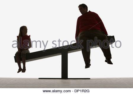 L'homme et la fille assise sur les extrémités d'une planche Banque D'Images