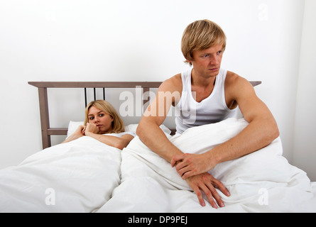 Angry Man sitting on bed with woman in house Banque D'Images