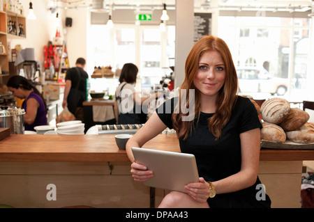 Portrait de jeune femme assise au comptoir de café Banque D'Images