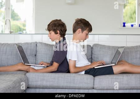 Frères au retour sur canapé à l'aide d'ordinateurs Banque D'Images
