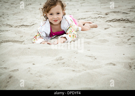 Portrait of young woman lying in sand Banque D'Images
