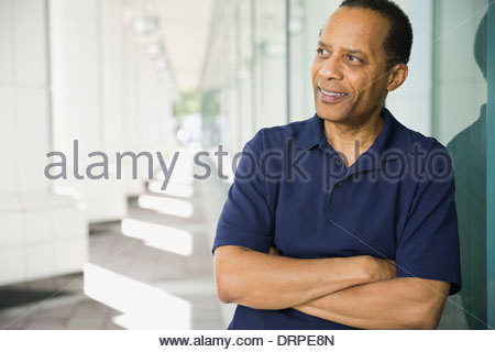 Thoughtful man leaning against window Banque D'Images
