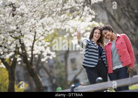 Temps de printemps. New York City park. Une jeune femme tenant un téléphone pour prendre une photo d'elle-même et Banque D'Images