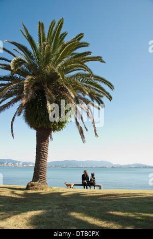 Mère et fille avec chien assis sur un banc, près de la mer Banque D'Images