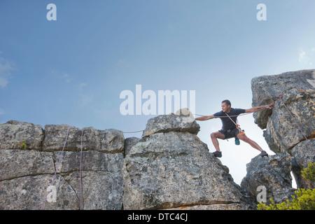 Jeune homme et pas à atteindre sur l'escalade Banque D'Images
