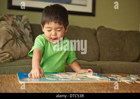 Puzzle Garçon jouant dans la salle de séjour Banque D'Images