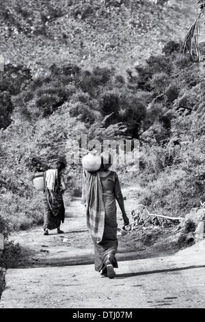Les femmes indiennes portant un pot en plastique avec de l'eau d'une pompe manuelle dans un village de l'Inde rurale. Banque D'Images