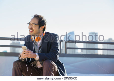 Smiling man wearing headphones listening to music outdoors Banque D'Images