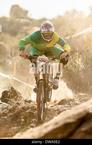 Vélo de montagne mâle course sur piste poussiéreuse, Fontana, California, USA Banque D'Images