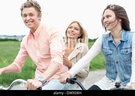 Portrait d'homme heureux appréciant en vélo avec des amis à la campagne Banque D'Images