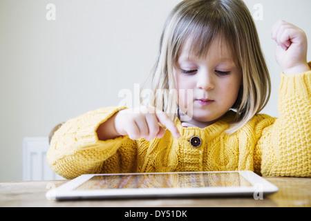 Jeune fille à la table de cuisine using digital tablet Banque D'Images