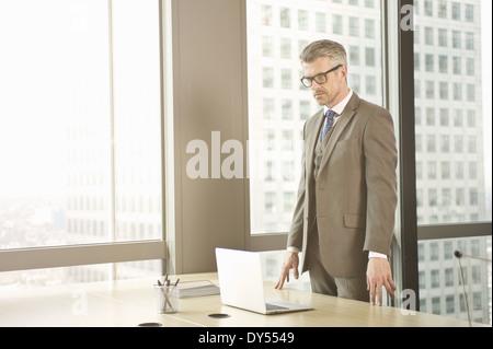 Businessman looking down at laptop sur office 24 Banque D'Images