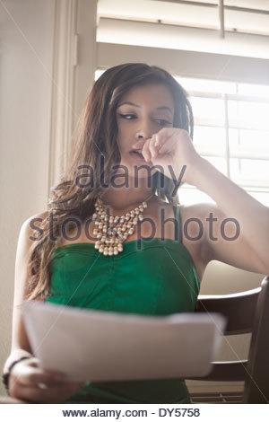 Jeune femme malheureuse avec la paperasse dans la main Banque D'Images