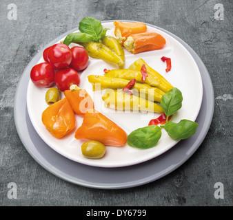 Antipasti de légumes , les poivrons avec le fromage à la crème , piment , olives en plaque sur fond gris Banque D'Images