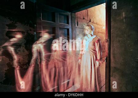 La figure fantomatique d'une jeune fille debout dans une porte dans le vrai Mary King's Close, une attraction touristique Banque D'Images
