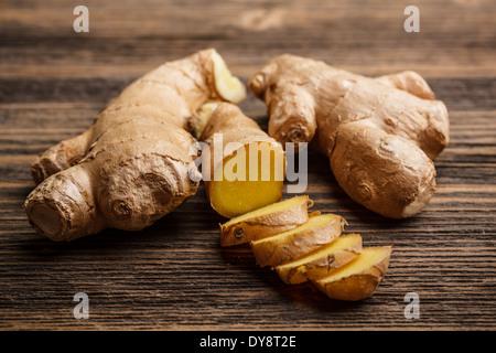 Gingembre frais, entières ou coupées en tranches sur fond de bois rustique Banque D'Images