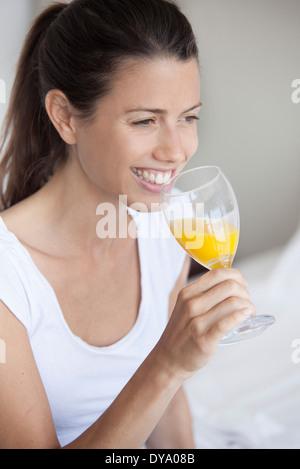 Jeune femme à boire le verre de jus d'orange Banque D'Images